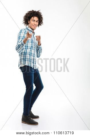 Full length portrait of a smiling afro american man with curly hair pointing fingers at camera isolated on a white background