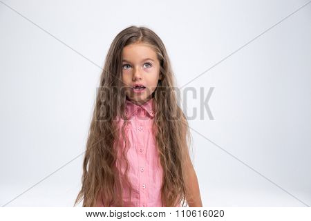 Portrait of amazed little girl looking away at copyspace isolated on a white background
