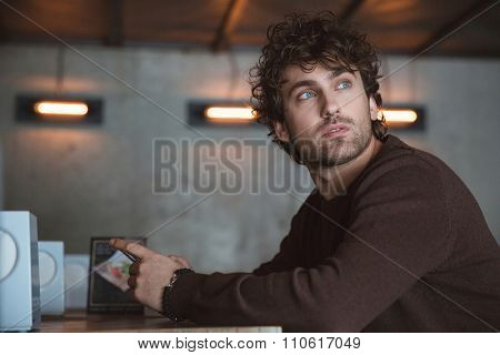 Thoughtful handsome pensive dreaming curly guy in brown sweetshirt sitting in cafe and using cellphone