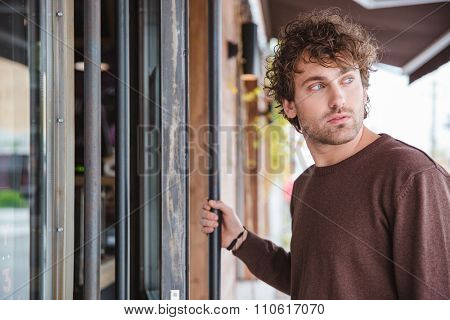 Pensive melancholic handsome curly young male in brown sweetshirt looking away and entering
