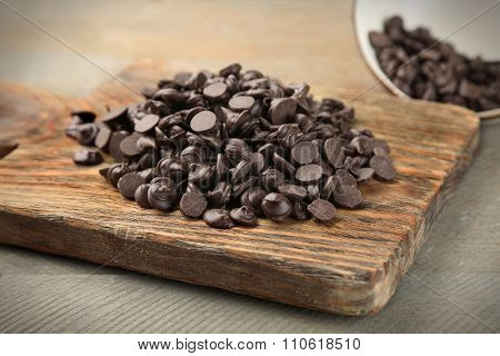 Chocolate morsels on wooden board