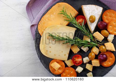 Round board with cheese, vegetables and rosemary on wooden table