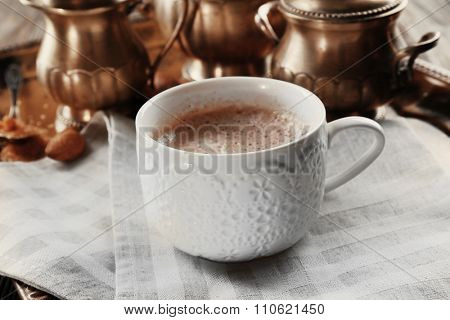 Cup of hot cacao on cotton serviette against silver service