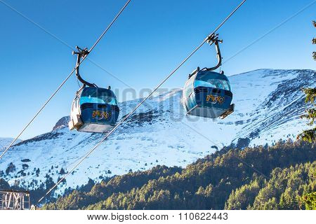 Two Bansko cable car cabins and snow mountains peaks, Bulgaria