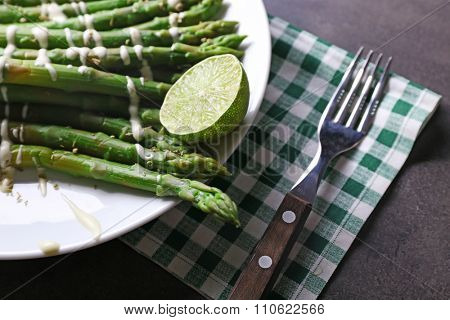 Fresh asparagus with lime on white plate with checkered cotton serviette on grey table