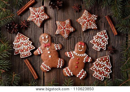 Gingerbread man and woman couple, fur trees, star, christmas cookies composition with xmas tree