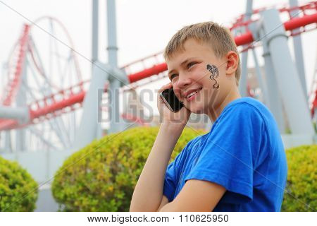 Boy talking on a mobile at an amusement park. Drawing a dragon on her cheek.