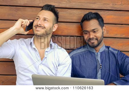 Two businessmen with mobile and laptop smiling