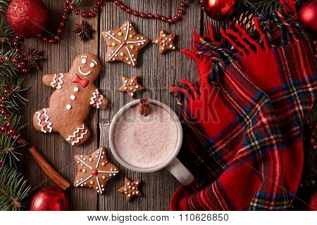 Cup of hot chocolate with gingerbread cookies and red plaid scarf