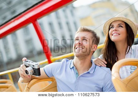 Young couple with a camera in a tour bus