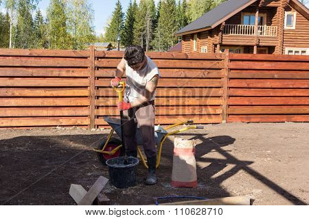 Man Mixes Cement With Shovel In The Bucket