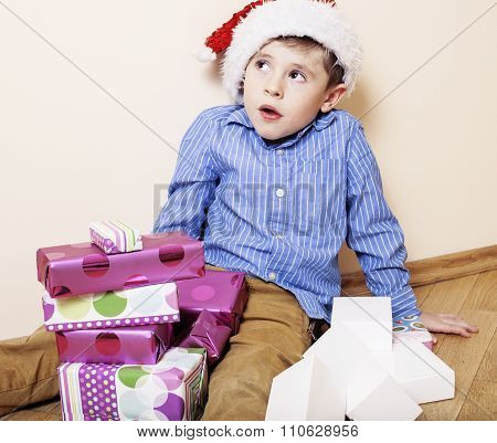 little cute boy with Christmas gifts at home. close up emotional face on boxes in santas red hat