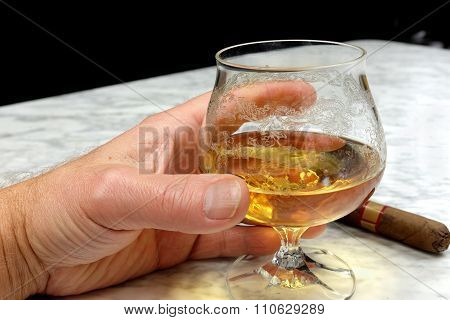 Hand Of A Man With A Cigar And A Glass Of Brandy