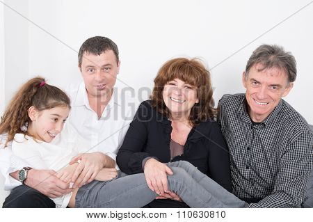 Multi Generation Family Sitting On Sofa In The Living Room