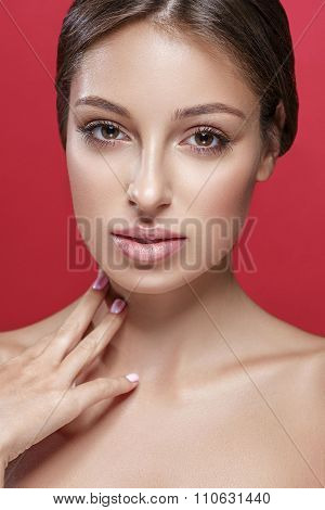 Beautiful woman touching her neck by fingers close up studio portrait on red