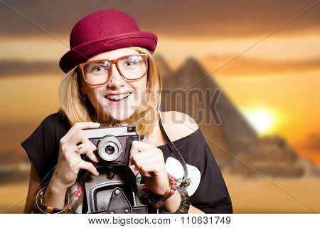 Pretty girl in glasses with camera on Egypt pyramid background.