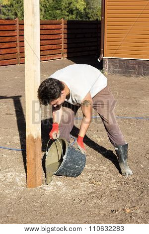 Man Pours A Bucket Of Cement Into A Hole