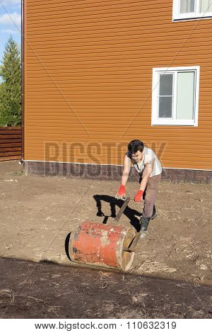 Man Compacts Soil With Hand Metal Roller