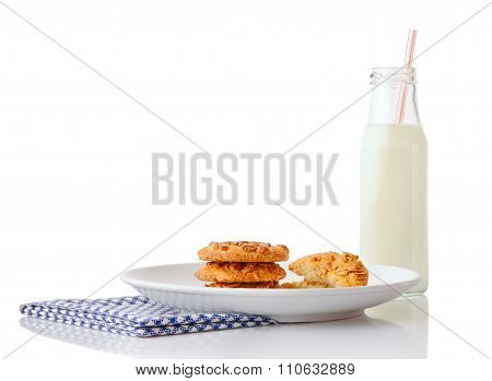 Stack of three homemade peanut butter cookies and halves of cookies on plate and bottle of milk