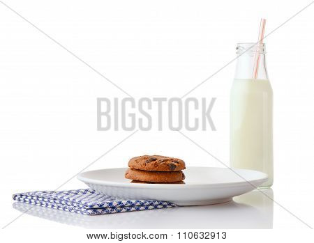 Stack of three homemade chocolate chip cookies on white ceramic plate on blue napkin and bottle of m