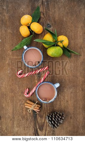 Christmas or New Year attributes. Fresh mandarins with leaves, cinnamon sticks, pine cone, hot choco