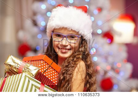 Young girl smiling with presents in fron of christmas tree