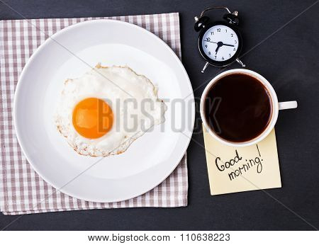 Fried Egg, Coffee And Alarm Clock On The Black Background