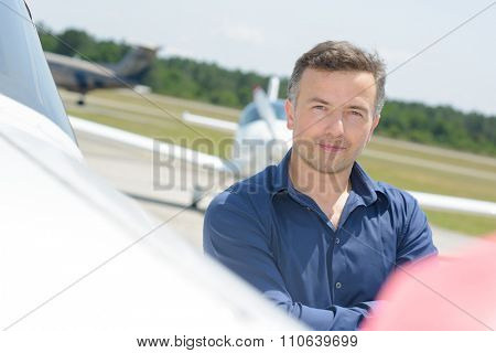 Portrait of man stood next to aircraft