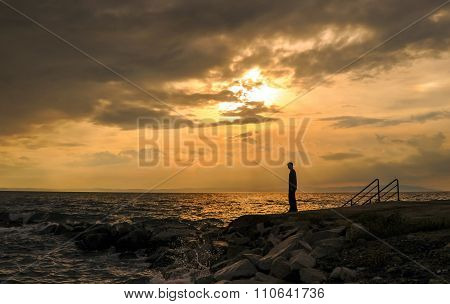 Silhouette Of Young Standing On Beach At Sunset
