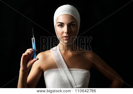 Young beautiful woman with a gauze bandage on her head and chest, holding a syringe, on black background