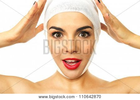 Young emotional woman with a gauze bandage on her head, isolated on white, close-up