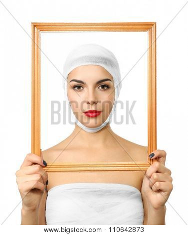 Young beautiful woman with a gauze bandage on her head and chest, holding a frame, isolated on white