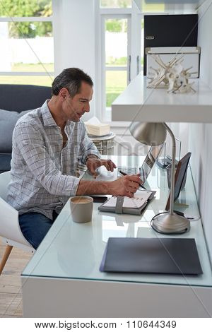 business man working at home office with laptop and writing on notebook