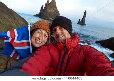 Tourist couple taking selfie at black sand beach south iceland, looking at reynisdrangar basalt sea stacks, waving icelandic flag