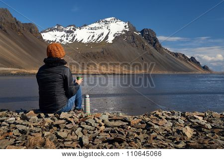 backview of anonymous traveller on holiday, stopping to have a drink from flask, looking out at the dramatic mountain view cliff landscape of iceland