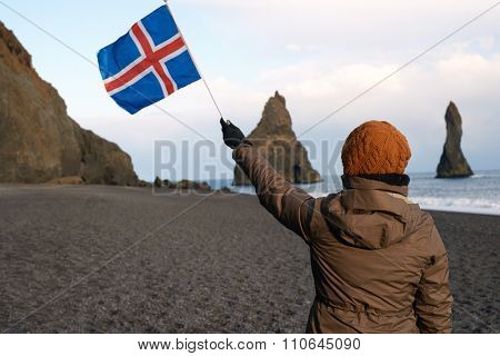 Independent traveller at black sand beach south iceland, looking at reynisfjara stone sea stacks, waving icelandic flag
