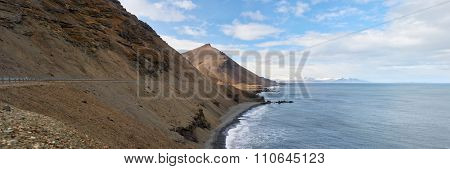 Panoramic of a long coastal road along main ring road in iceland, with dramatic steep cliffs into the ocean
