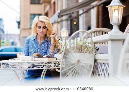 Young gorgeous lady enjoying coffee while relaxing in restaurant in the fresh air