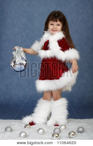 Little Girl In Christmas Costume With Glass Ball