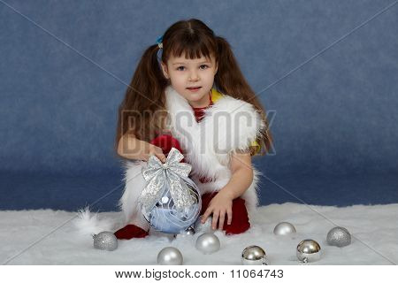 Child Sits On Blue With Christmas Tree Ball