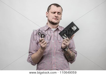 Man with audio and video cassettes
