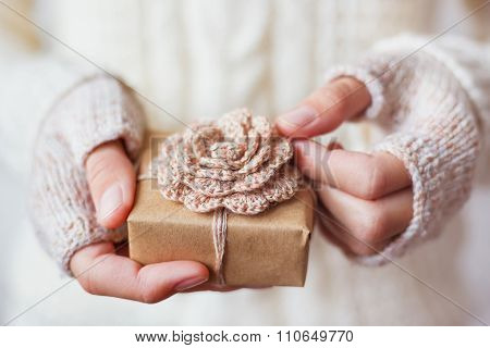 Woman In White Knitted Sweater Holding A Present. Gift Is Packed with Crocheted Flower