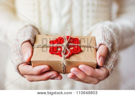 Woman In White Knitted Sweater And Mitts Holding A Present. Gift Is Packed In Craft Paper