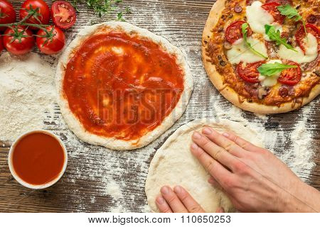 Italian pizza preparation. Hands making pizza dough on wooden table.
