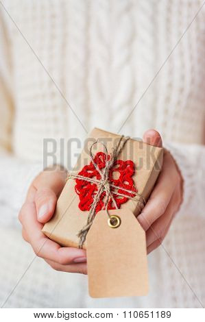 Woman In Knitted Sweater Holding A Present. Gift Is Packed In Craft Paper With Hand Made Snowflake