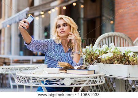 Young attractive blonde lady making self portrait with her smartphone digital camera