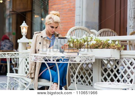 Charming female reading something on her touch pad while she relaxing in coffee shop