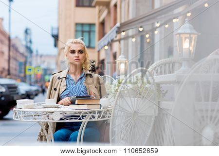 Attractive blonde female looking away while rest after work on digital tablet during recreation time