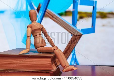 Wooden dummy, mannequin or man figurine sit on book with many blue frames On background