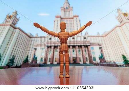 Wooden man against backdrop of the main building Of Lomonosov Moscow State University on Sparrow Hil